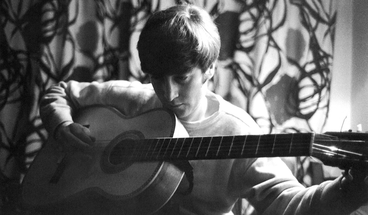John Lennon playing an acoustic guitar at home, 1964